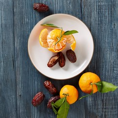 Plate of dried figs and ripe oranges on wood background