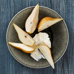 Bowl of pears with cream on wood background