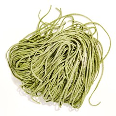 Pile of green linguine pasta on white background