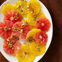 Plate of grapefruit slices topped with nuts on wood background