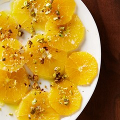 Plate of orange slices topped with nuts on wood background