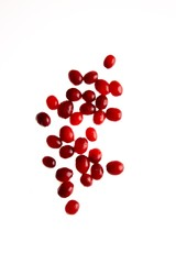 Red fruit seeds on white background