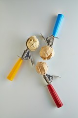 Scoops of ice cream in three scoopers studio shot