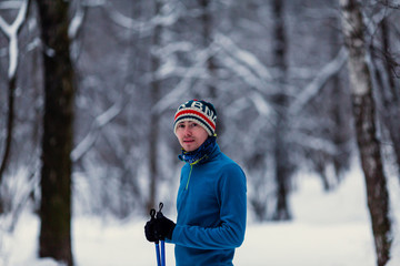 Portrait of male skier in forest at winter