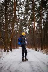 Side view of woman with backpack over winter forest