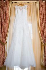 wedding dress hanging on window at hotel room.