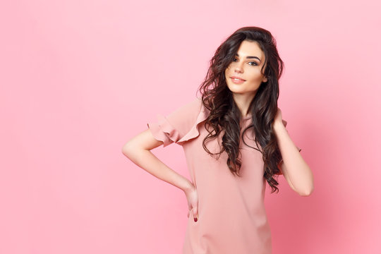 Beautiful fashionable girl with long curly hair in a pink dress in the studio on a pink background. Advertising, hair products, beauty salon, cosmetics, clothing. Fashion, boutique. Pink.