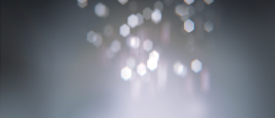 Realistic bokeh with geometric hexagonal iris. Soft  slightly pink abstract background with light particles out of focus. Long horizontal format.