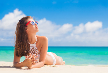 woman in bikini and sunglassesrelaxing on tropical beach/