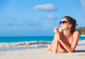 woman in sunglasses and swimsuit at beach. Praslin, Seycheles