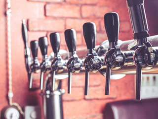 Close-up of beer tap in bar on a background of red brick wall. Selective focus