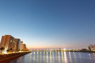 朝焼けに染まる大淀川とビル群