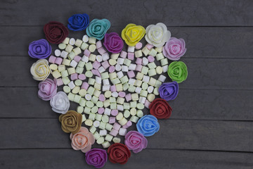 sweet marshmallows in heart shape decorated with flowers on wood background. valentine day concept.