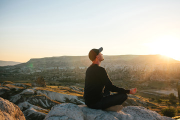 A man practices yoga at the top of the mountain at sunrise. Practices of relaxation.