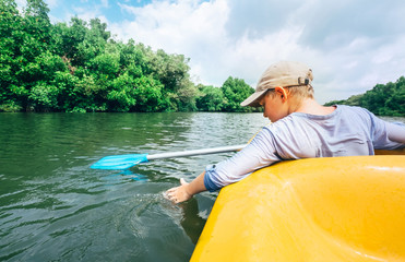 Boy sailing in canoe on tropical lagoon - active leisure time