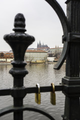 View of Vltava river and Prague castle from the other side of the river through the fence with love locks