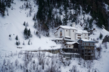 Church in mountains covered with snow and winter forest near Mont Blanc Alpes, Italy