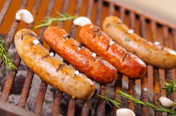 Close up of four grilling sausages on barbecue grill with some species. BBQ in the garden. Bavarian sausages