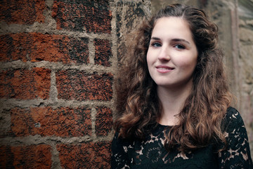 Portrait Of Happy Beautiful Young Woman Against Brick Wall