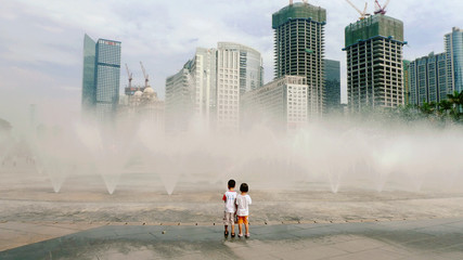 Full Length Of Boy And Girl Standing By Fountains Against Cityscape