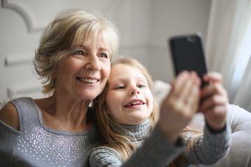 Grandmother and granddaughter using a smartphone
