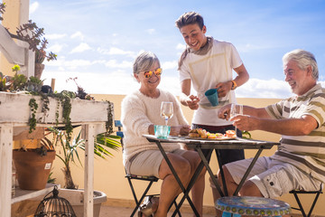 A 70-year-old senior and a 14-year-old boy can enjoy the sunny day outdoors on a terrace with food and drink. The blue sky is the background.