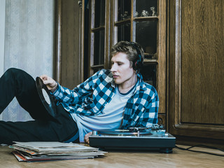 portrait of young man at home listening to the vinyl records, relaxing and dreaning