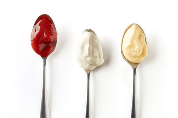 Three sauces in spoons isolated on white, from above