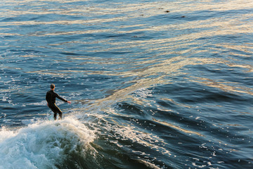 Overhead view of surfer on wave during a beautiful golden sunrise in California