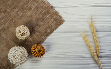 Wheat grains and decorative wooden spheres on white wooden background