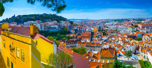Summertime sunshine day cityscape panoramic view of town, Sao Jorge Castle, and all historic old centre in Lisbon, Portugal.