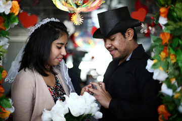 A couple exchange rings during a symbolic wedding event on Valentine's Day in Mexico City