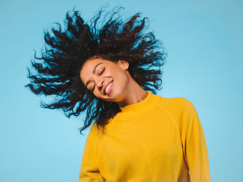 mixed race black woman portrait with big afro curly hair on blue background dancing and with hairstyle flying in air