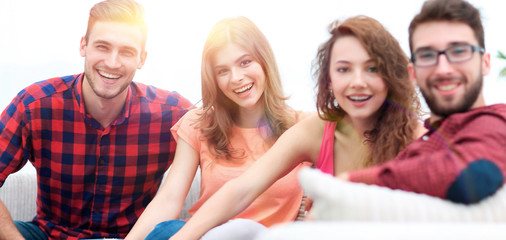 group of cheerful friends sitting on sofa