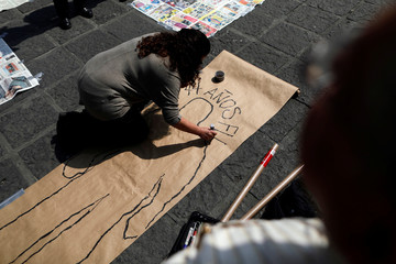 A demonstrator marks a silhouette on a paper in memory of missing people, on Santo Domingo square in Mexico City