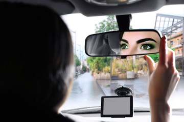 Young woman adjusting rear view mirror while driving car on city road