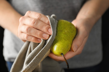 Woman wiping pear, closeup