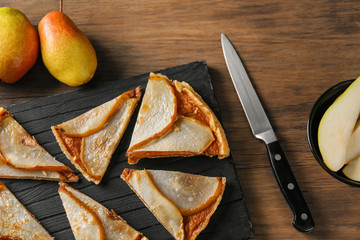 Slices of delicious pear tart on wooden board