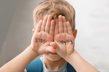 """Little boy with words """"Stop bullying"""" on light background"""