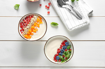 Yogurt with fruits in dishes on wooden table