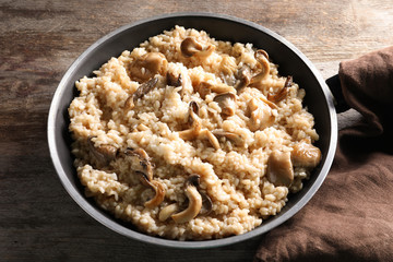 Frying pan with risotto and mushrooms on table