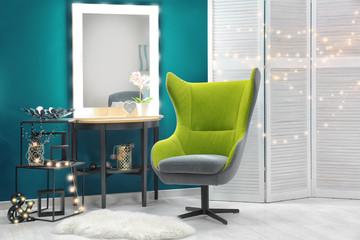 Stylish interior with trendy armchair near shaded spruce wall