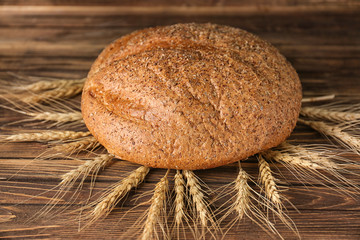 Fresh tasty bread and spikelets on wooden background