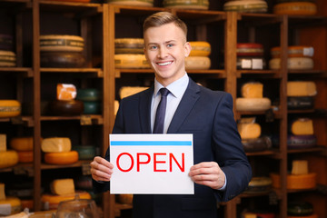 "Business owner holding ""OPEN"" sign in his store"