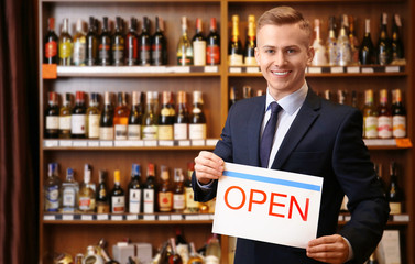 """Business owner holding """"OPEN"""" sign in his store"""