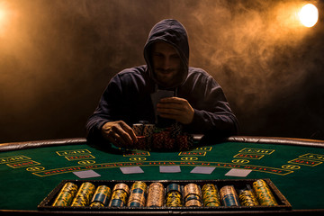 Portrait of a professional poker player sitting at poker table