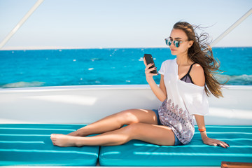 Young beautiful brunette girl using phone while sitting on the yacht