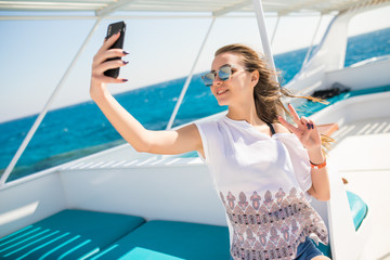 Young beautiful brunette girl making selfie using phone while sitting on the yacht