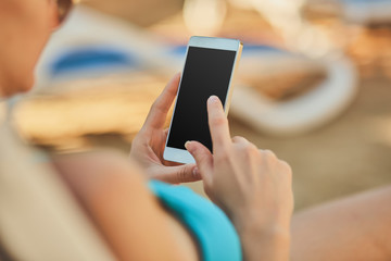 Close up view of a young attractive woman on holiday laying down on a white chaise-longue, holding and using a smartphone.