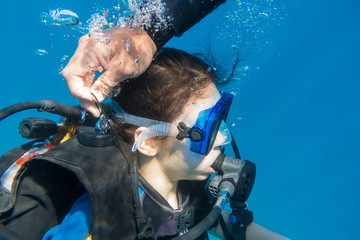 Scuba instructor opened the air valve on wetsuit for immerse